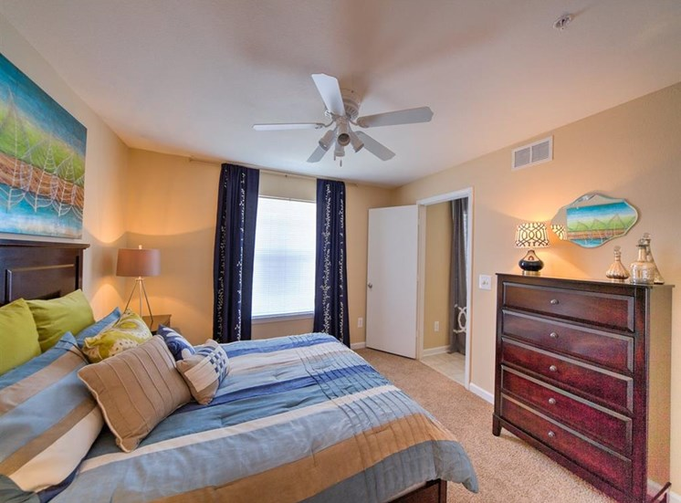 Furnished model bedroom with carpet flooring, multi speed ceiling fan, drawer set, and large window for natural lighting