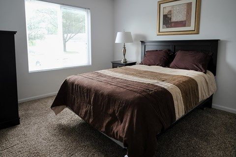 Premium unit master bedroom, mature trees outside window, natural lighting, in Regency apartments Bettendorf, Iowa