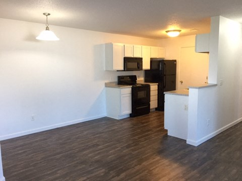 spacious dining room, bright white clean cabinets, wood flooring, premium countertops and appliances at regency apartments in Bettendorf Iowa