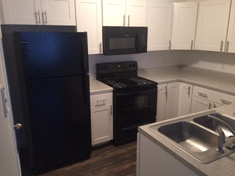 Premium kitchen counter, bright white cabinets, and appliances in Regency apartments Bettendorf, Iowa
