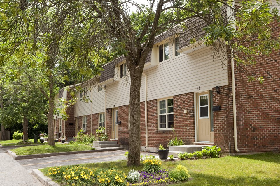 Several townhouse exteriors next to each other with neatly clipped green grass and lush trees.