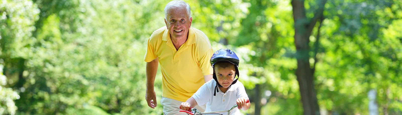 Grandfather with grandchild riding a bike in a peaceful forest