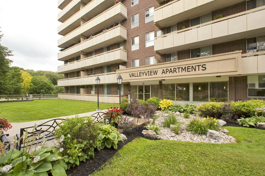 Exterior entrance of Valleyview Apartments with wooden benches and healthy flowerbeds
