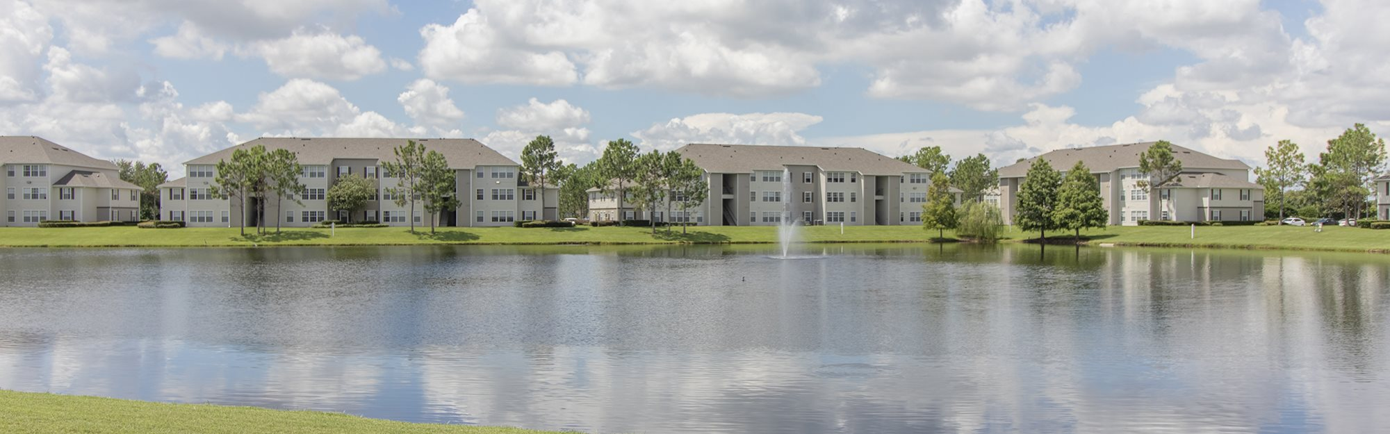 Lee Vista Apartments for rent in Orlando, FL. Make this community your new home or visit other ConcordRENTS communities at ConcordRENTS.com. Building exterior with lake