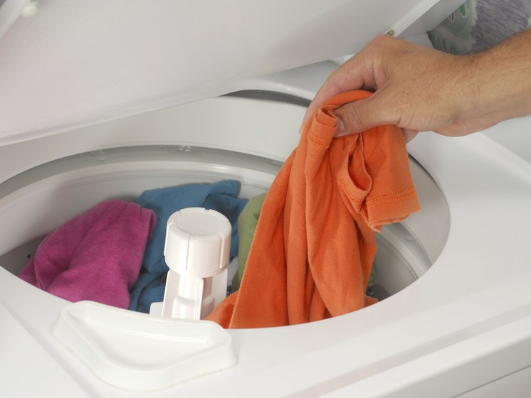 person putting clothes in washing machine-Legacy Apartments, Pittsburgh, PA 15219
