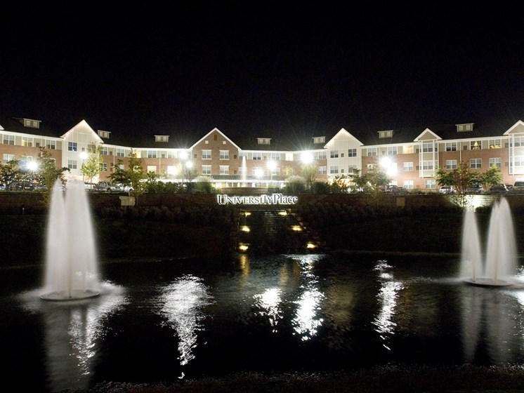 Apartment buildings and pond at night-Senior Living at University Place Apartments, Memphis, TN 38104