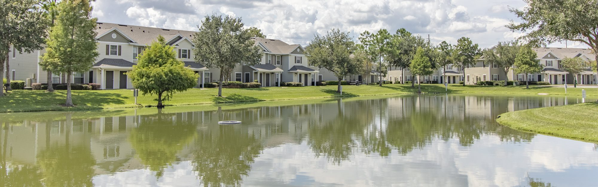 Belle Isle Apartments for rent in Orlando, FL. Make this community your new home or visit other Concord Rents communities at ConcordRents.com. Exterior with lake and buildings