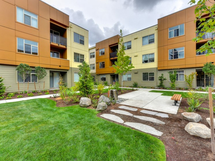 Luxury Apartment Community Building Exterior and Landscaping with Bench