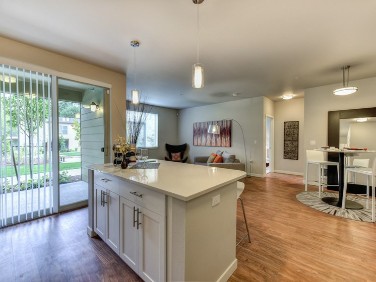 Luxury Apartment Community Kitchen Island with Dining Area and View of Private Patio