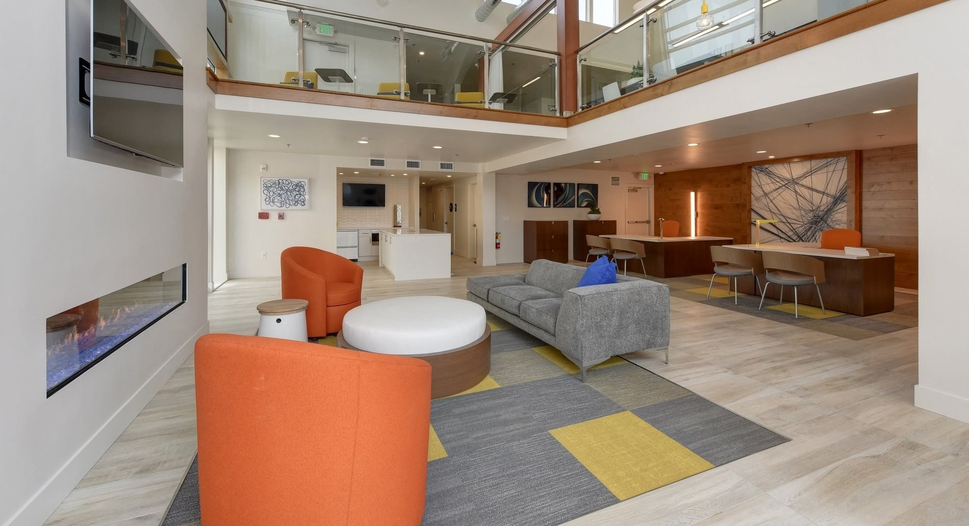 Clubhouse Lounge Area with Orange Seats, Gray Sofa, Flat Screen Television and Second Floor