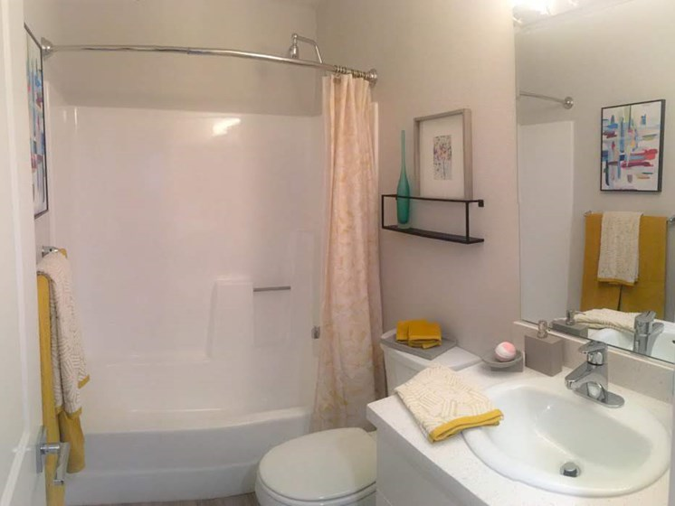 Bathroom with Toilet, Wood Cabinets, Full Vanity, and Shower Curtains