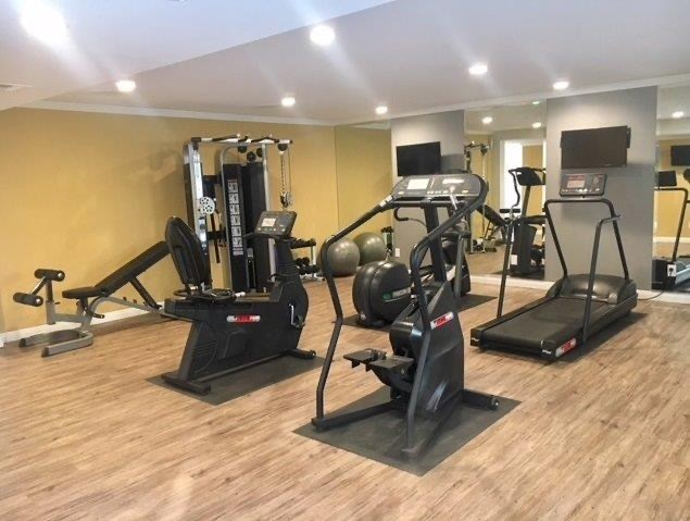 Fitness Center with Hardwood Inspired Floor, Ellipticals, Ceiling Lights and Treadmills