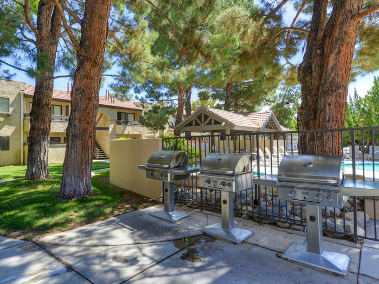 Outdoor Community BBQ Area with 3 Grills, Gate Blocking Pool and Trees