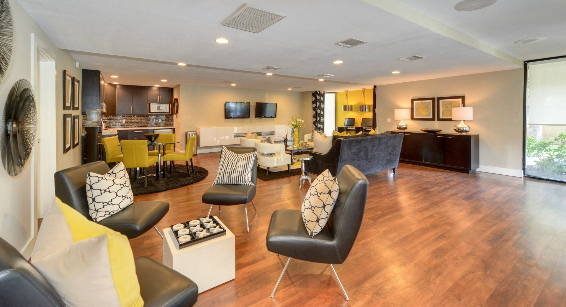 Clubhouse Lounge Area with Hardwood Inspired Floors, Black Sofa Chairs, Windows, and View of Kitchen Area