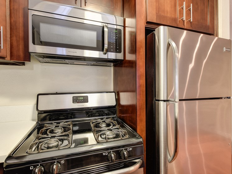 Kitchen with Wood Cabinets and Stainless Steel Appliances Refrigerator Oven Microwave Stove