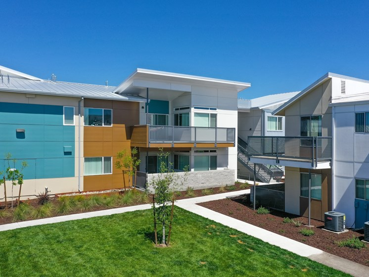 Apartment Exterior with Walking Path, Grass, Wood Chip Floor, Blue Apartment Exterior