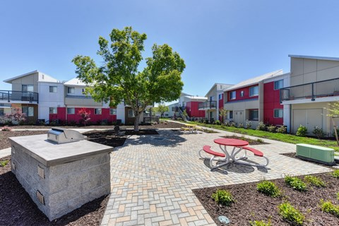 Outdoor Lounge Space with Red Picnic Table, Trees, Wood Chip Floor, Apartment Exterior