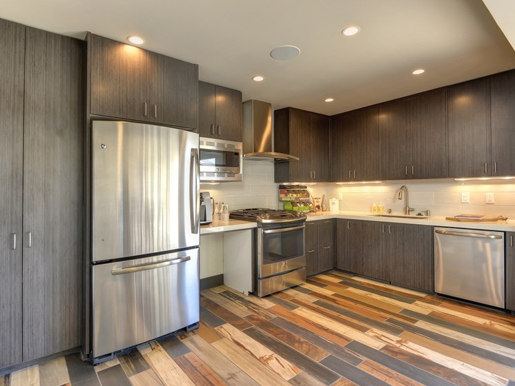 Leasing Office Kitchen with Hardwood Inspired Floors and Stainless Steel Appliances On-Site Management Available 24/7