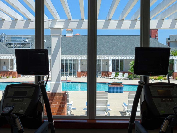 fitness center has a view of the pool at 1200 Acqua Luxury Apartments in Petersburg