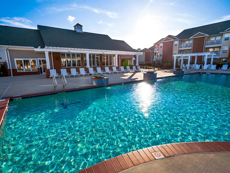 sun setting over the pool behide the clubhouse at 1200 Acqua Apartment homes near Fort Lee Virginia