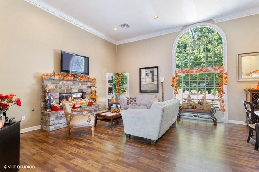 Club house with seating area with arm chairs, coffee table, love seat, couch, and wood style flooring.