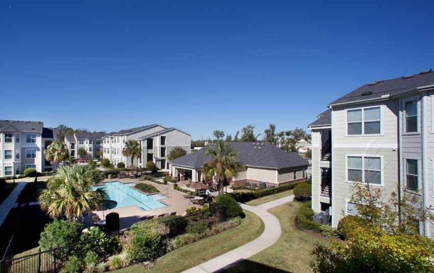 Ariel view of community with apartment buildings, sidewalks, grassy ares, club house, pool area and the sky in the background.
