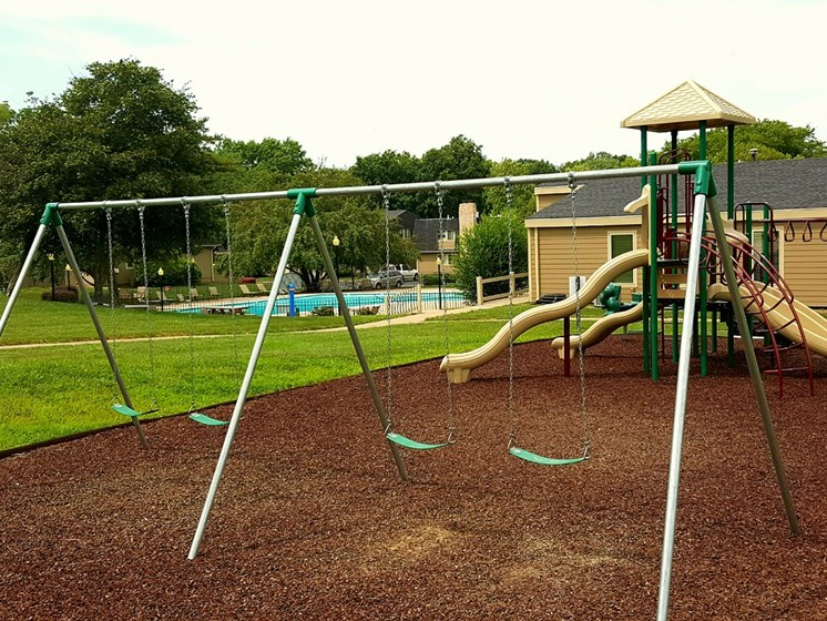 Apartments with swingset at The Oaks at Prairie View Apartments in North Kansas City, MO