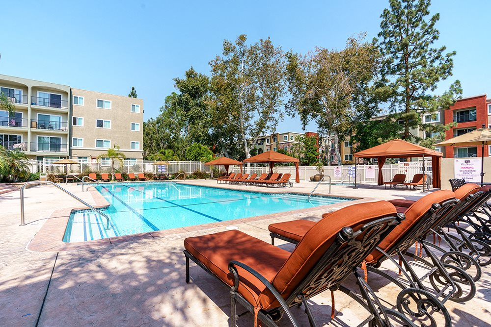 Woodland Hills CA Luxury Apartments The Reserve at Warner Center Resort Style Pool with Shaded Cabanas and Lounge Chairs