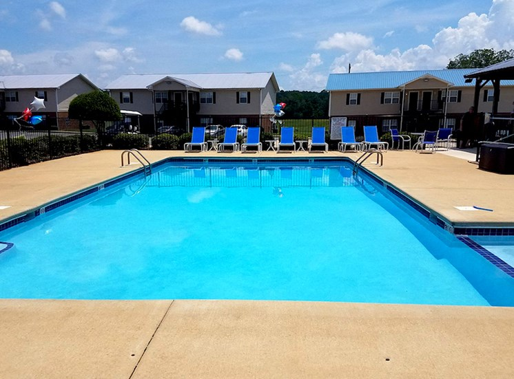 sparkling pool with large sundeck and deck chairs