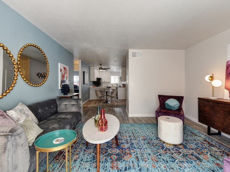 Living Room with Blue Pattern Rug, White Table, Gray Sofa, Purple Chair and Round Wall Mirrors