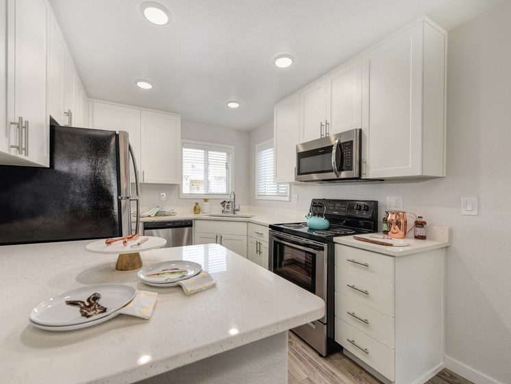 Kitchen with White Countertop, White Cabinets, Microwave and Refrigerator