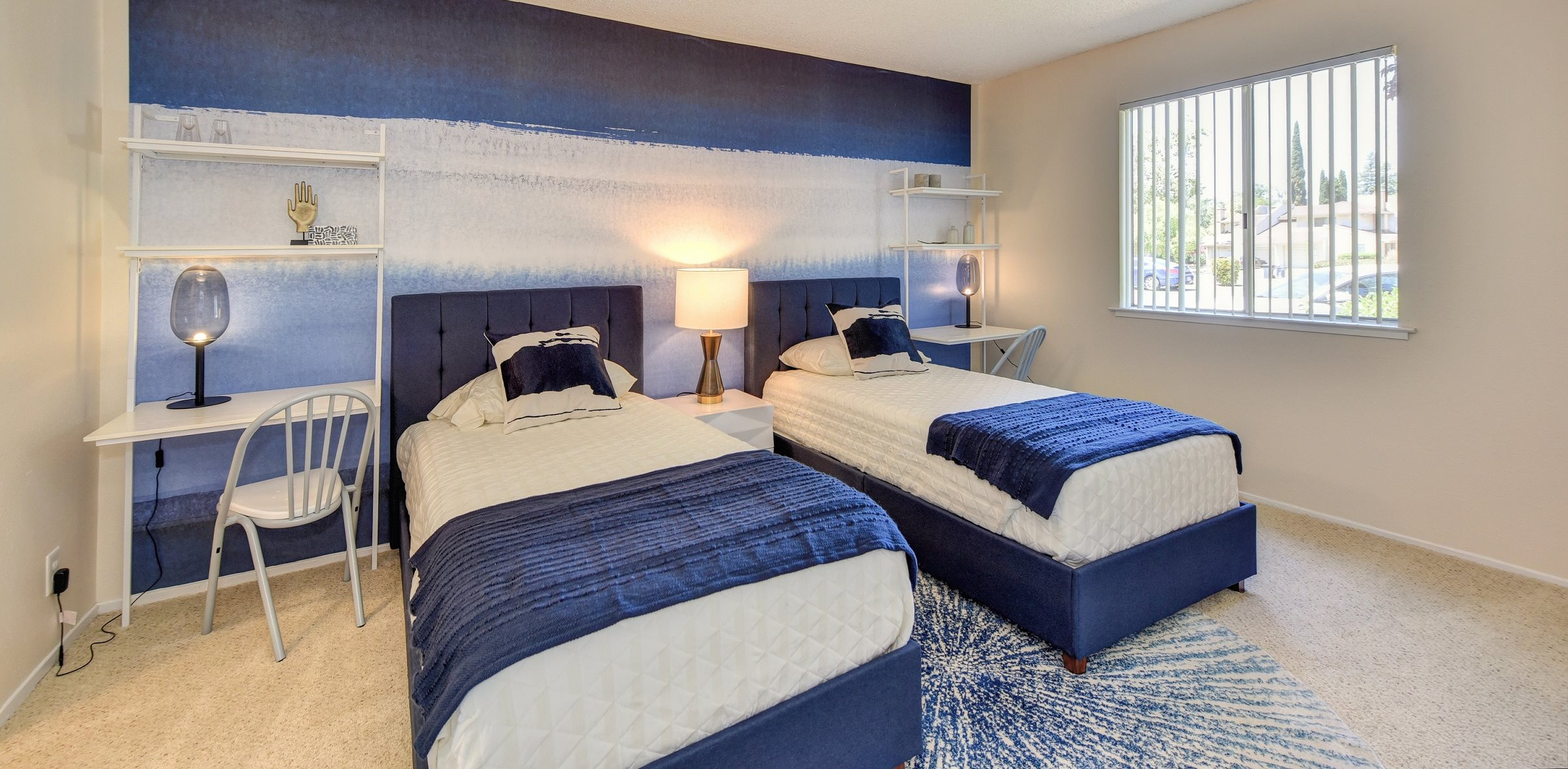 Model bedroom with blue and white accent wall and matching bedding.  Small desks on the sides of each of the two beds.
