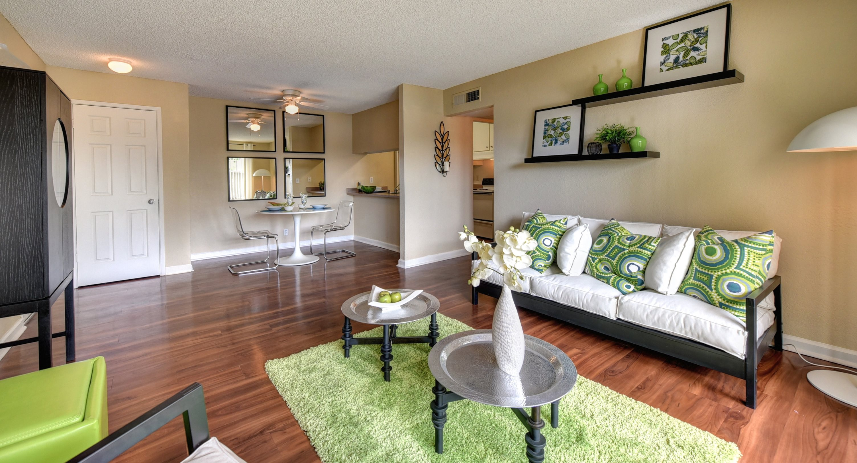 Living Room with White Sofa, Green Pillows, Hardwood Inspired Floor, with Green Carpet