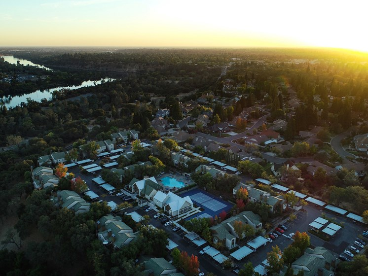Drone Shot at Dusk with Apartment Roofs, Trees and Roads