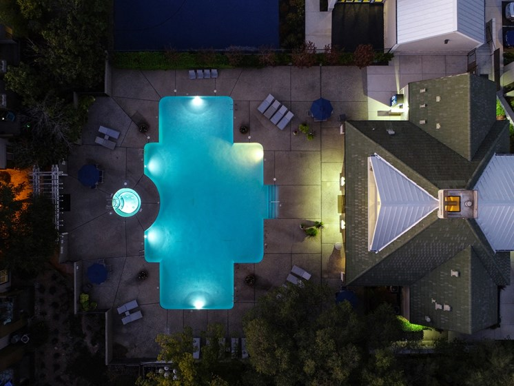 Nightime Drone of Pool Area with Lounge Chairs, Trees and Plants
