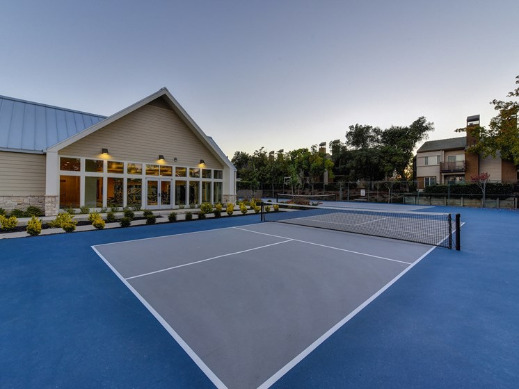 Tennis Courts with Fitness Center Exterior, Trees, and Bushes