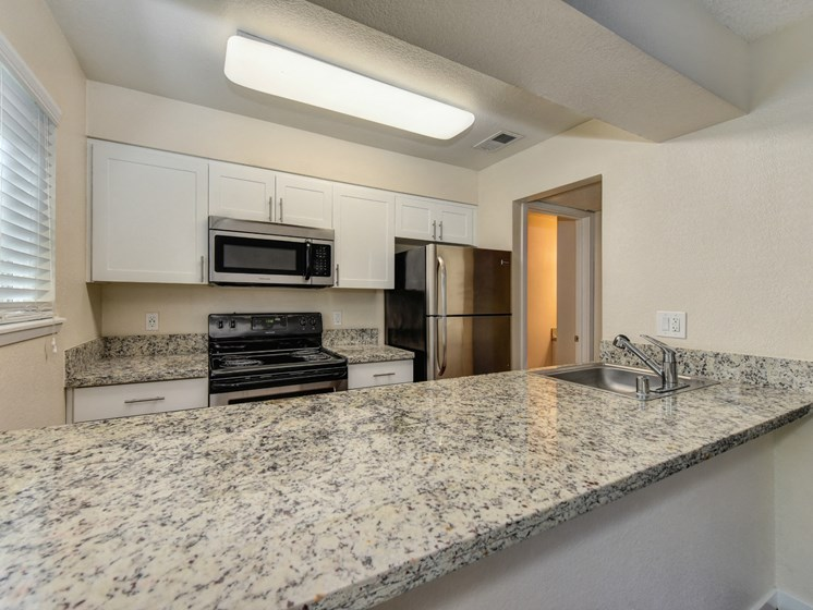 Luxury Apartment Community Kitchen with Granite Counters and Stainless Steel Appliances
