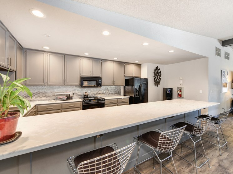 Clubhouse Kitchen with Bar Seating, White Counter, Cabinets and Refrigerator