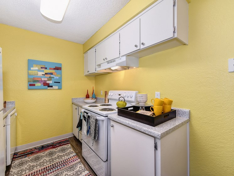 Kitchen with Stove with Yellow Walls, Stove, Hardwood Inspired Floor and White Cabinets