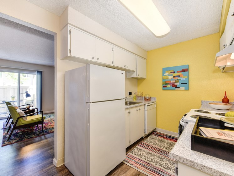 Kitchen with Refrigerator, Bright Yellow Accent Walls, Hardwood Inspired Floors and Refrigerator