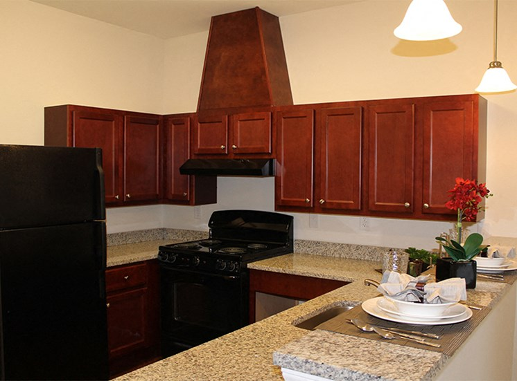 Kitchen at Arden Woods with black appliances and granite counter tops.