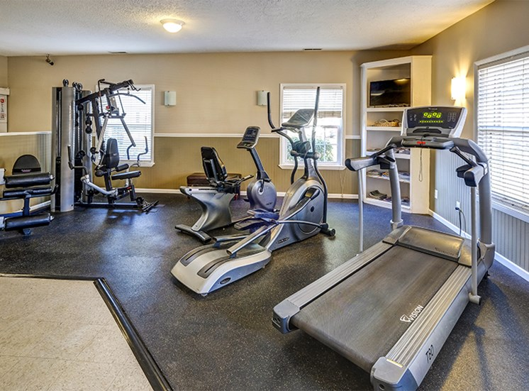 Fitness center with elliptical, treadmill, and muscle training equipment.