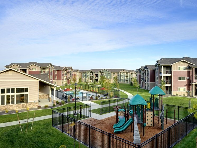 Playground with grass by apt buildings  Apts in Colorado Springs, CO | Copper Creek