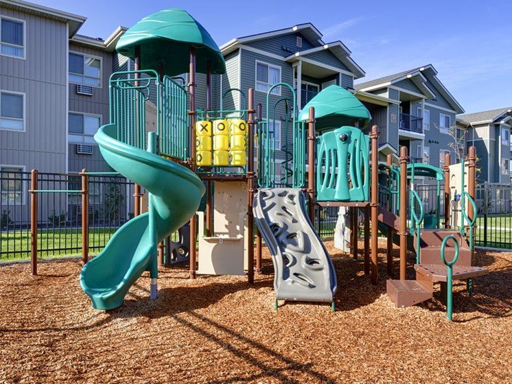 Playground with grass by apt buildings  Colorado Springs, CO 80916 | Copper Creek Apts For Rent