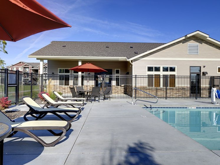 Pool with lounge chairs andApt building in backgroundApartments in Colorado Springs, Co  Copper Creek Apartments