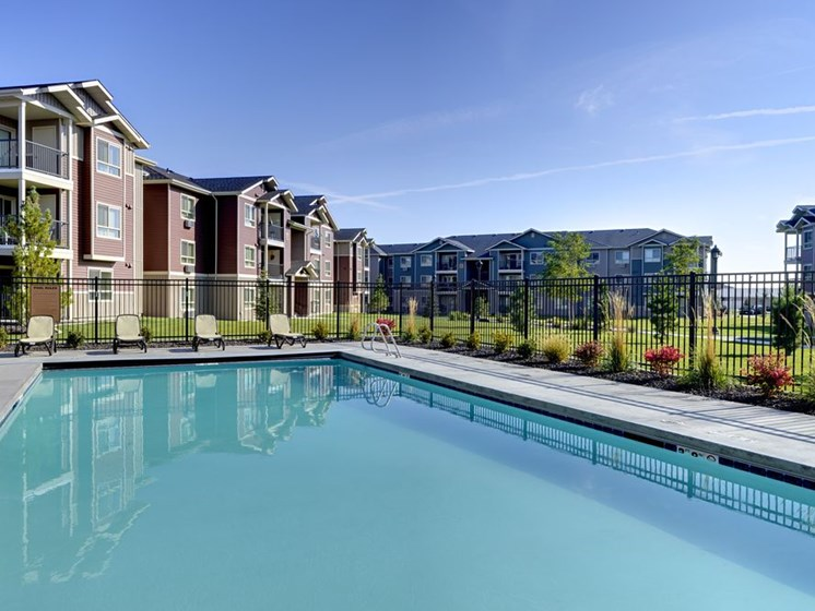 Pool with Apt building in background Colorado Springs, CO Apts For Rent | Copper Creek