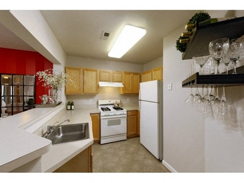 Kitchen Area with sink, oven, microwave, and refrigerator