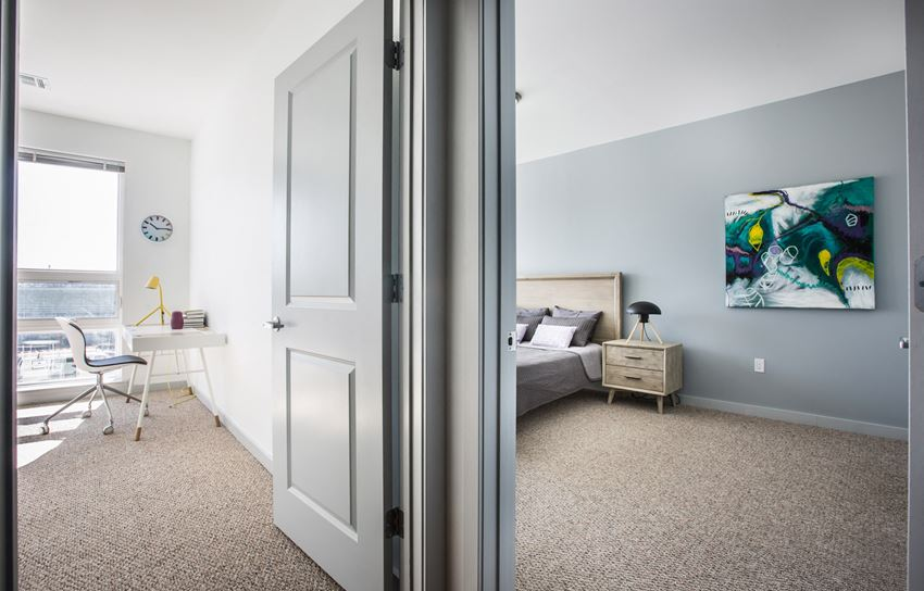 View of two bedrooms with carpeted floors, one bedroom and one office