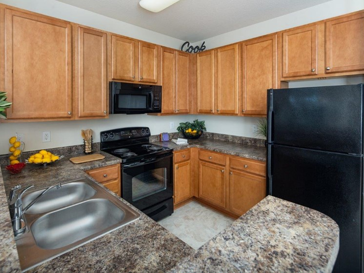 Kitchen With Sink, Refrigerator And Modern Appliances at Abberly Village Apartment Homes by HHHunt, South Carolina, 29169