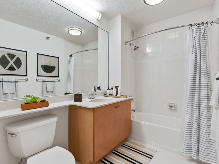 Bathroom with white tiling, cabinetry, a large mirror and black and white decorative accents